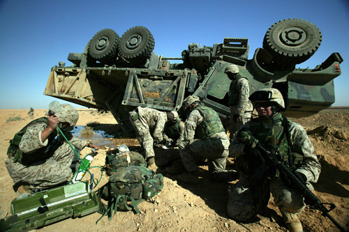 U.S. Marine Corps photo by Lance Cpl. TJ Kaemmerer | Navy Hospital Corpsmen, Marines and Navy Chaplain tend to injured Marines when the seven-ton truck they were driving overturned during a supply convoy to Camp Korean Village in western Iraq.