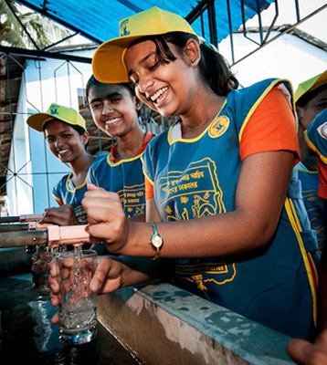© Jeff D. Friesen   WATSAN committee members in their Water For People uniforms fill glasses with clean water at Purbachal Balika Vidyapith Girls' School, Nadia, West Bengal.
