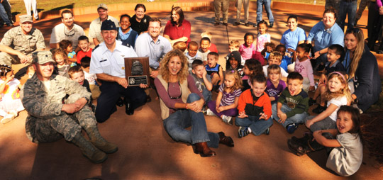Photo Credit: U.S. Air Force Base youth give a big growl at the awards ceremony. (L to R seated in front- Col. Dave Novy; Col. James Slife, Wing Commander; Kristal Walsh, Natural Resources Manager)