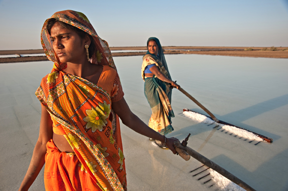 Image courtesy ami vitali/Ripple Effect Images | Women raking salt in India.