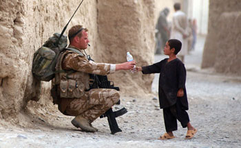 Photo courtesy NATO | A UK soldier hands a bottle of water to a local child in Afghanistan.